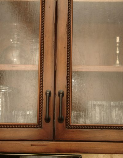 Distressed stained finish was applied to kitchen cabinets.